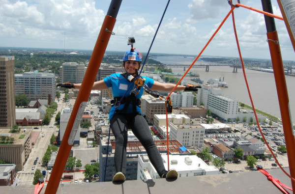 "Jaci Sanchez smiles and lets go of her rappelling rig after going ""Over the Edge for Adoption"" from the roof of the 310 foot tall One American Place tower in downtown Baton Rouge on June 18. The device automatically locks if the rappeller lets go of it for obvious safety reasons. Photo by Mark H. Hunter"