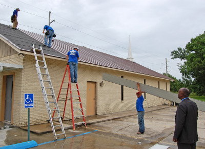 Rev. Donald Hunter watches a roofing crew as they finish up installing a new roof on New Beginning Baptist Church. The job was paid for by The Chapel as part of its annual Easter offering to support other local faith ministries. photo by mark h hunter