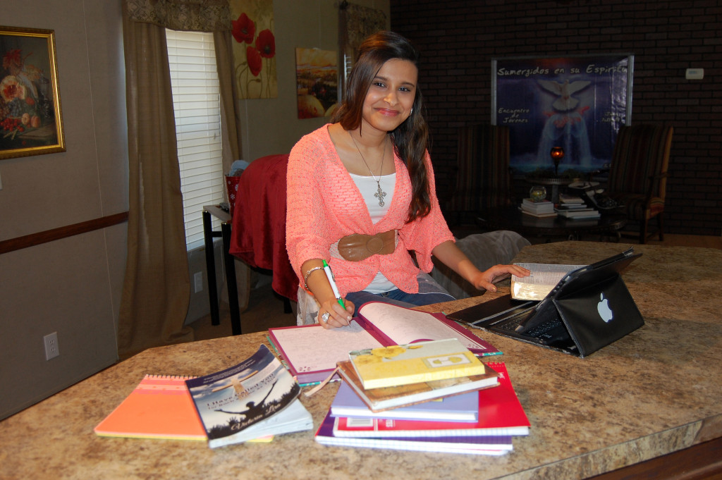 "Teen devotional writer Victoria Lira covers her mother's kitchen counter with her Bible, laptop and notebooks as she works on compiling a second book to follow her first, (in front) ""I Have Called You for Such a Time as This."" Photo by Mark H. Hunter"