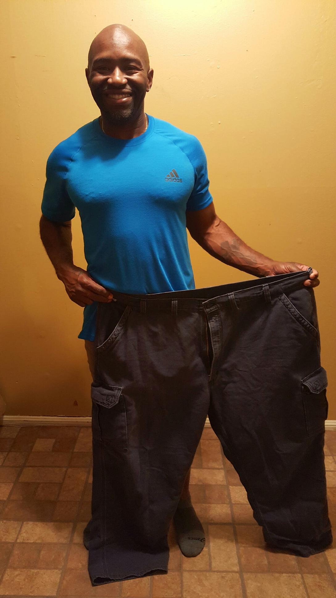 Pedro holds a pair of his old pants showing just how much weight he has lost.